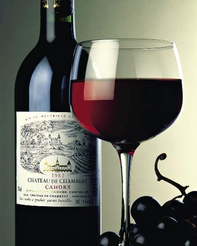 Eine Flasche Rotwein, Rotwein im Glas und Weintrauben