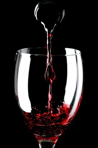 Aus der Flasche in Glas Rotwein eingiessen