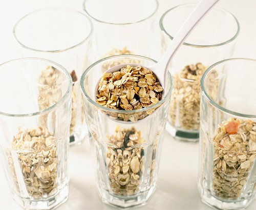 spooning muesli into glasses (filmed recipe: fromage frais with fruit and muesli)