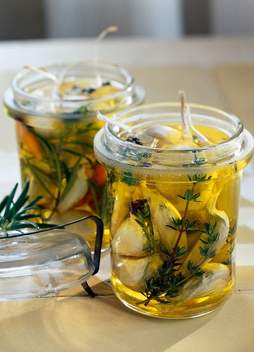 Garlic marinating in oil with rosemary and thyme