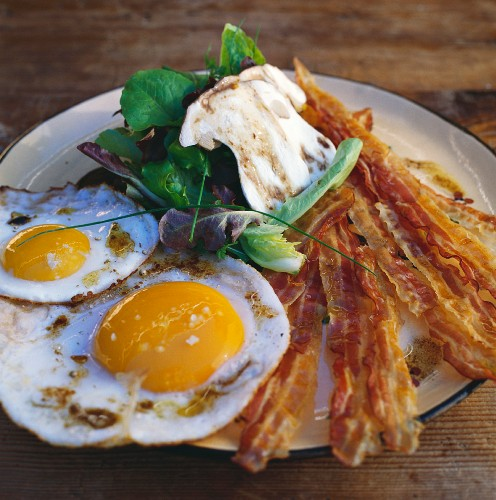 Fried eggs with bacon and a mushroom salad