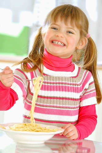 Young girl enjoying a plate of pasta