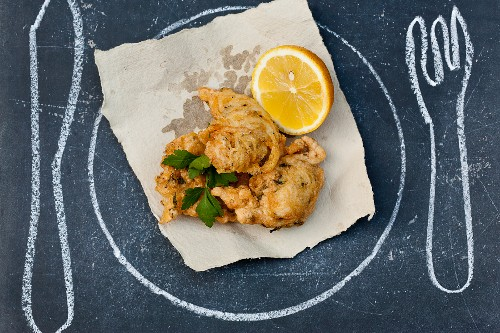"""""""Deep-fried battered fish ;Plate ,knife and fork drawn on the table"""""""