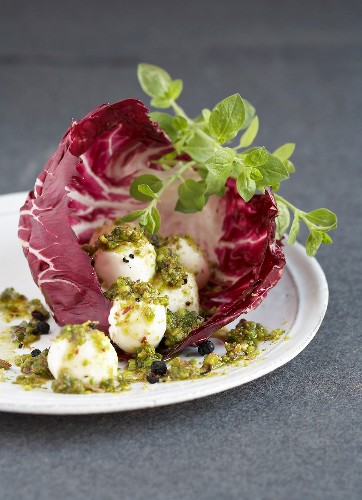 Small mozzarella balls with crushed pistachios in a red chicory leaf