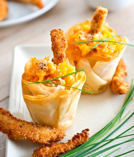 Small crisp carrot bites and chicken fingers coated in crushed hazelnuts and parmesan