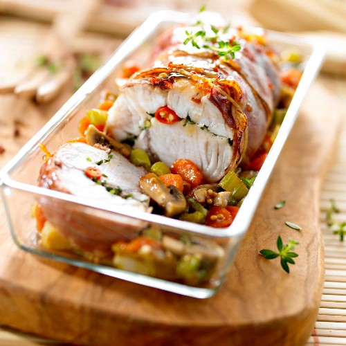 Roasted silure glane carp wrapped in ham with vegetables