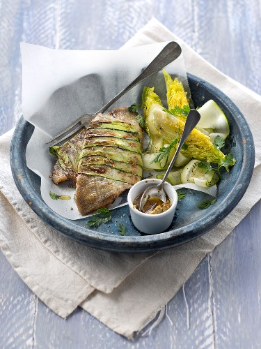 Sea bream fillets wrapped in thin strips of zucchinis,lettuce salad and pesto sauce