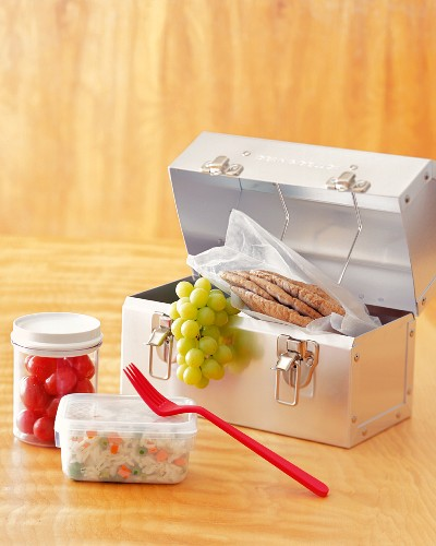 A Metal Lunchbox with Green Grapes and Pita Bread with Rice Salad and Tomatoes in Plastic Containers