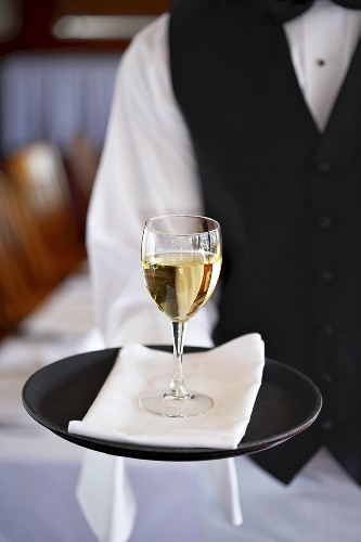 Waiter serving a glass of white wine