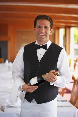 Waiter holding bottle of sparkling wine by table in restaurant