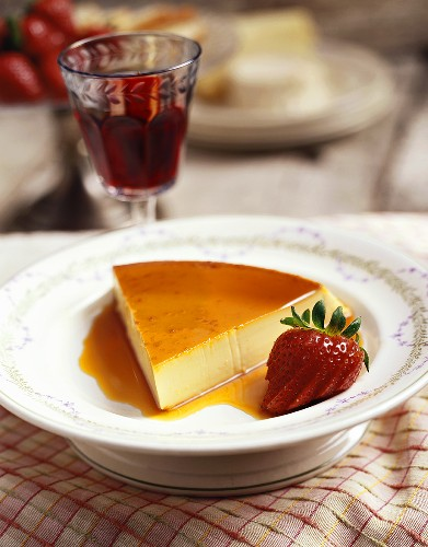 A slice of caramel custard with a glass of red wine