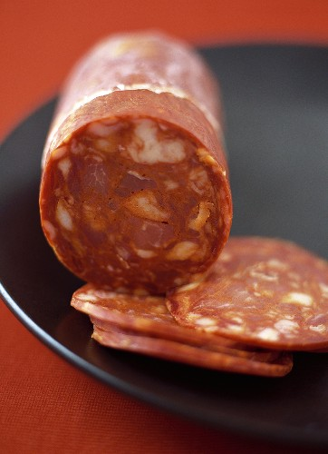 Chorizo with Slices on a Black Plate, Close Up