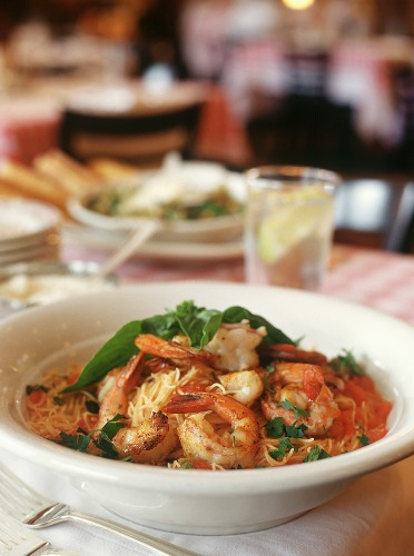 Shrimp Over Angel Hair Pasta with Tomato Sauce and Basil on a Restaurant Table