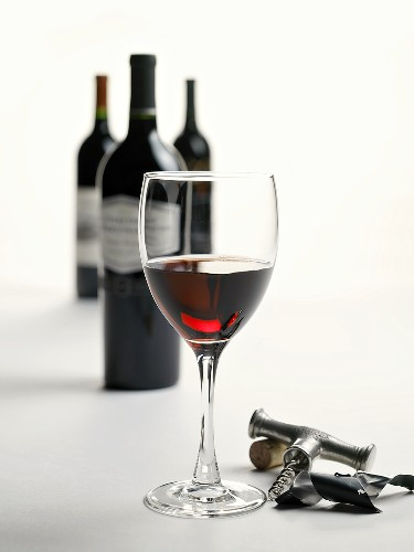 A Glass of Red Wine with Corkscrew, Cork and Wine Bottles