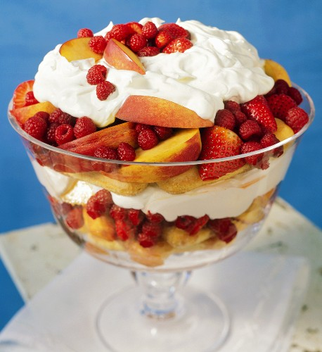 Trifle with peaches, berries, cream and sponge fingers