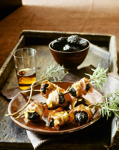 Bacon-wrapped prunes with rosemary & glass of sherry on tray