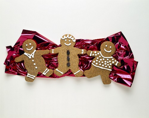 Three Gingerbread Men Resting on Foil Paper