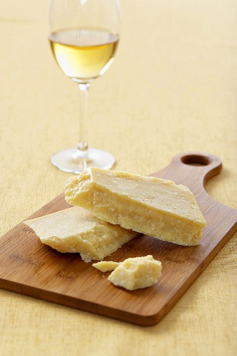 Parmesan Cheese on a Cutting Board with a Glass of White Wine