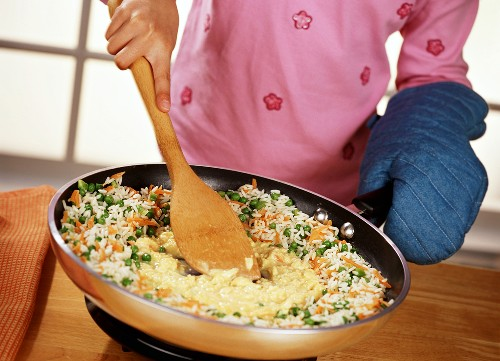 Child Stirring Scrambled Eggs into a Wok Full of Rice Stir Fry, Wearing Oven Mitt While Holding Handle