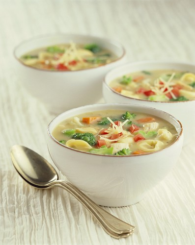Three Bowls of Chicken Tortellini Soup Topped with Shredded Parmesan Cheese