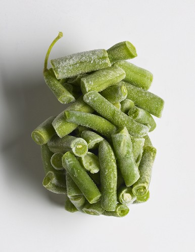 Cluster of Frozen Green Beans with Frost on a White Background