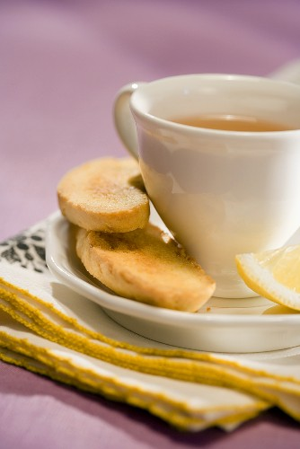 Cup of Tea on a Saucer with Biscotti and Lemon Wedge