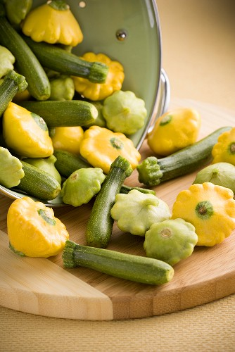 Assorted Baby Squash Spilling From a Colander; Patty Pan and Courgettes