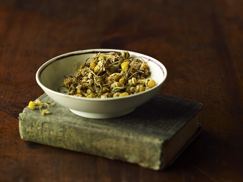 A bowl of dried camomile flowers on an old book
