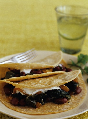 Two Pinto Bean and Poblano Tacos on a Plate; Glass of Water with Lime