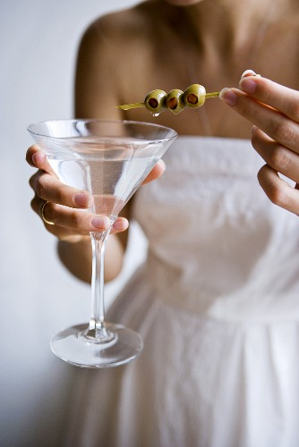 Woman in White Dress Holding a Martini and Olives