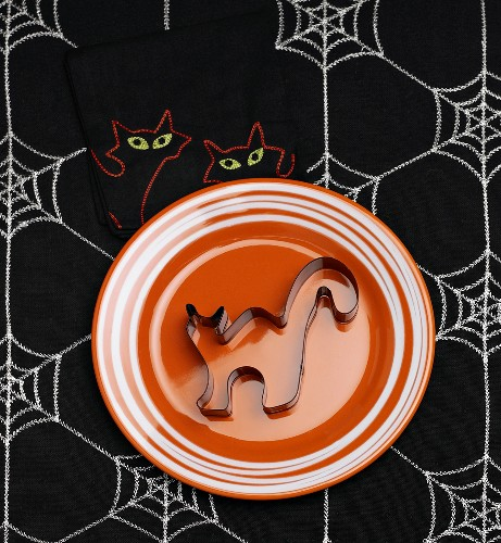 Black Cat Cookie Cutter on Orange Plate on Halloween Table Cloth