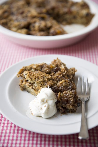 Serving of Spiced Bread Pudding with Whipped Cream; Spiced Bread Pudding in Baking Dish