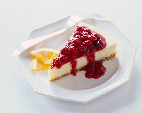 Slice of Cheesecake with Cherry Sauce Topping; On a White Plate