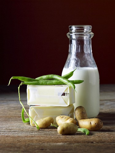 An arrangement of butter, milk, green beans and potatoes