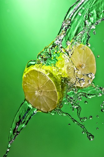 Halved Lime in Water Splashing Across Green Background