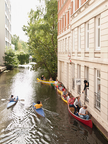 Canoes waiting in front of a cafe on a Alster canal, Hanseatic City of Hamburg, Germany