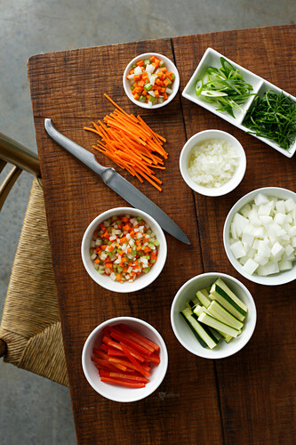 Bowls of chopped vegetables on table