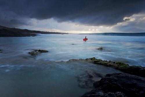 Hawaii, Big Island, Kona Coast, Kua Bay, Bodyboarder checking out stormy surf, Long exposure - showing motion.