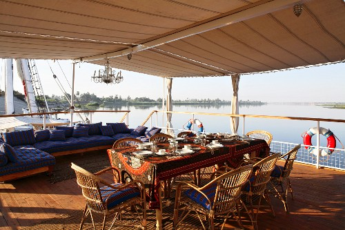 A coffee break on a covered sundeck on a boat with a view over the River Nile, Egypt