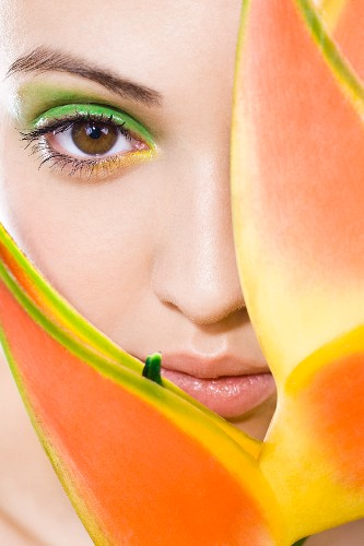 A young woman with green make-up peeking out from behind a plant