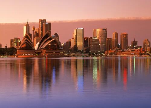 Sydney skyline mit Opera House bei Sonnenaufgang, Spiegelung von Gebäuden im Wasser, Sydney, New South Wales, Australien
