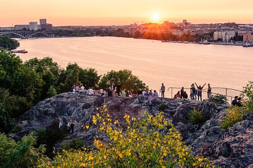 Blick von Soedermalm Skinnerviksparken, Menschen geniessen den Sonnenuntergang , Stockholm, Schweden