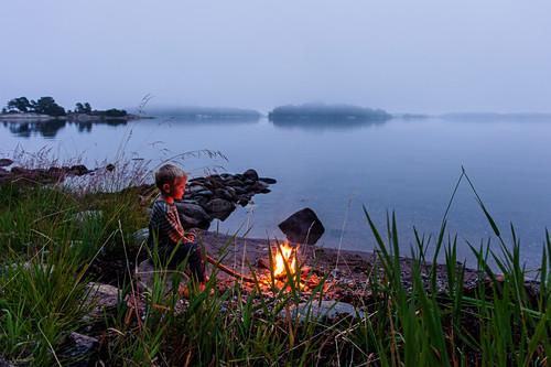 kleiner Junge am Lagerfeuer im Schärengarten Insel Fiskhamn , Stockholm, Schweden