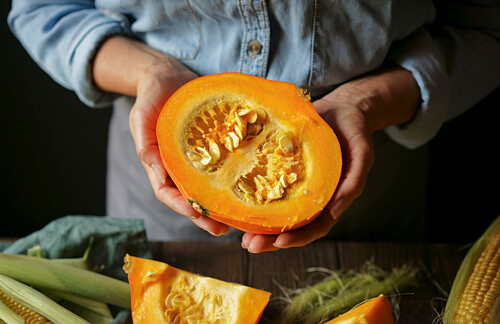 Hands of Caucasian woman showing sliced squash