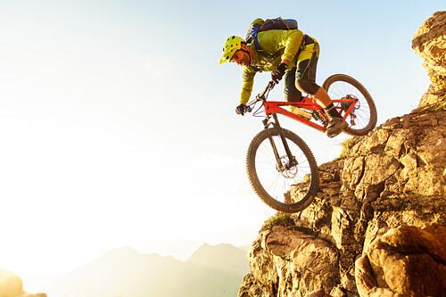 Middle aged man drops a steep rock clif on his mountainbike, Kitzbühel Alps, Tyrol, Austria