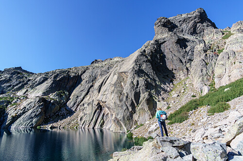 Young woman with climbing gear has a look at her next climbing objective, a multi pitch route in the Restonica valley, Corsica