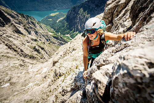 Smiling young woman with climbing gear ascends the Watzmann east face, views to lake Königsee, St. Bartholomä, Berchtesgaden, Bavaria, Germany