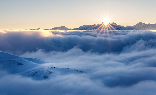 Sunrise over a sea of clouds, hut is overlooking the clouds, Brenner mountains, Stubai Alps, Tyrol, Austria