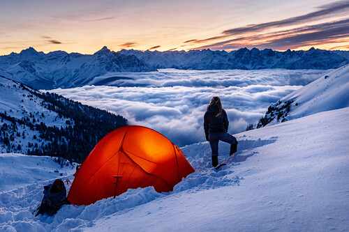 Young woman is standing next to an orange, enlightet tent in the snow, sea of clouds, wintery mountains, Innsbruck, Tyrol, Austria