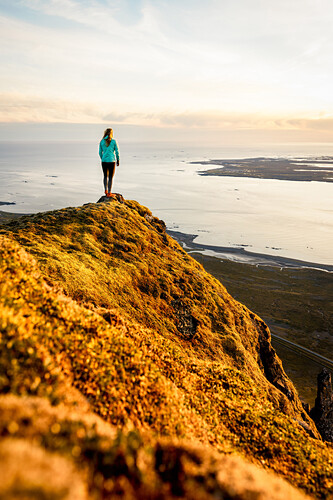 Young woman on a moosy rock high above the ocean, sunset, Hofn, Vesturland, Iceland